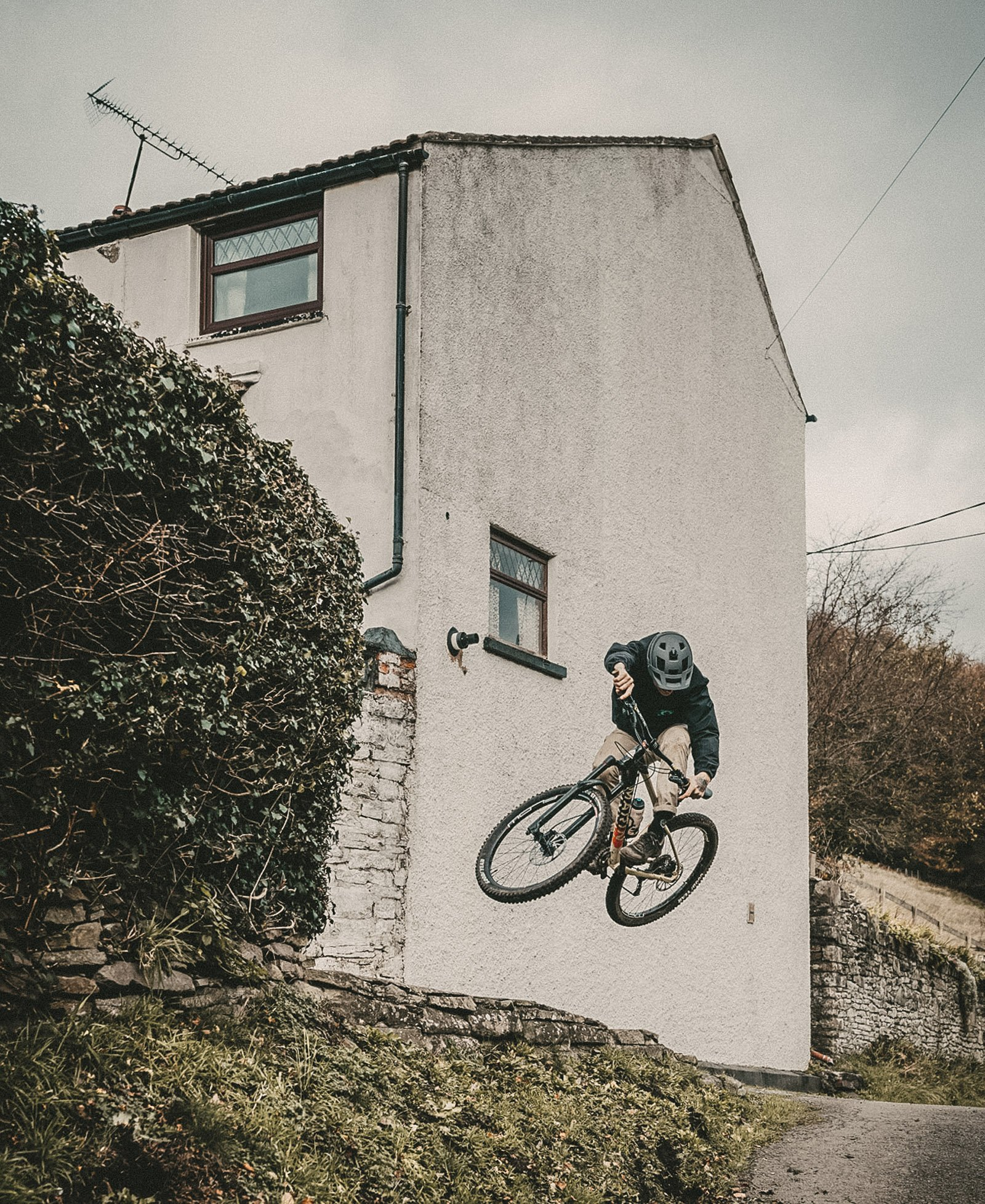 Moutain biker jumping from house
