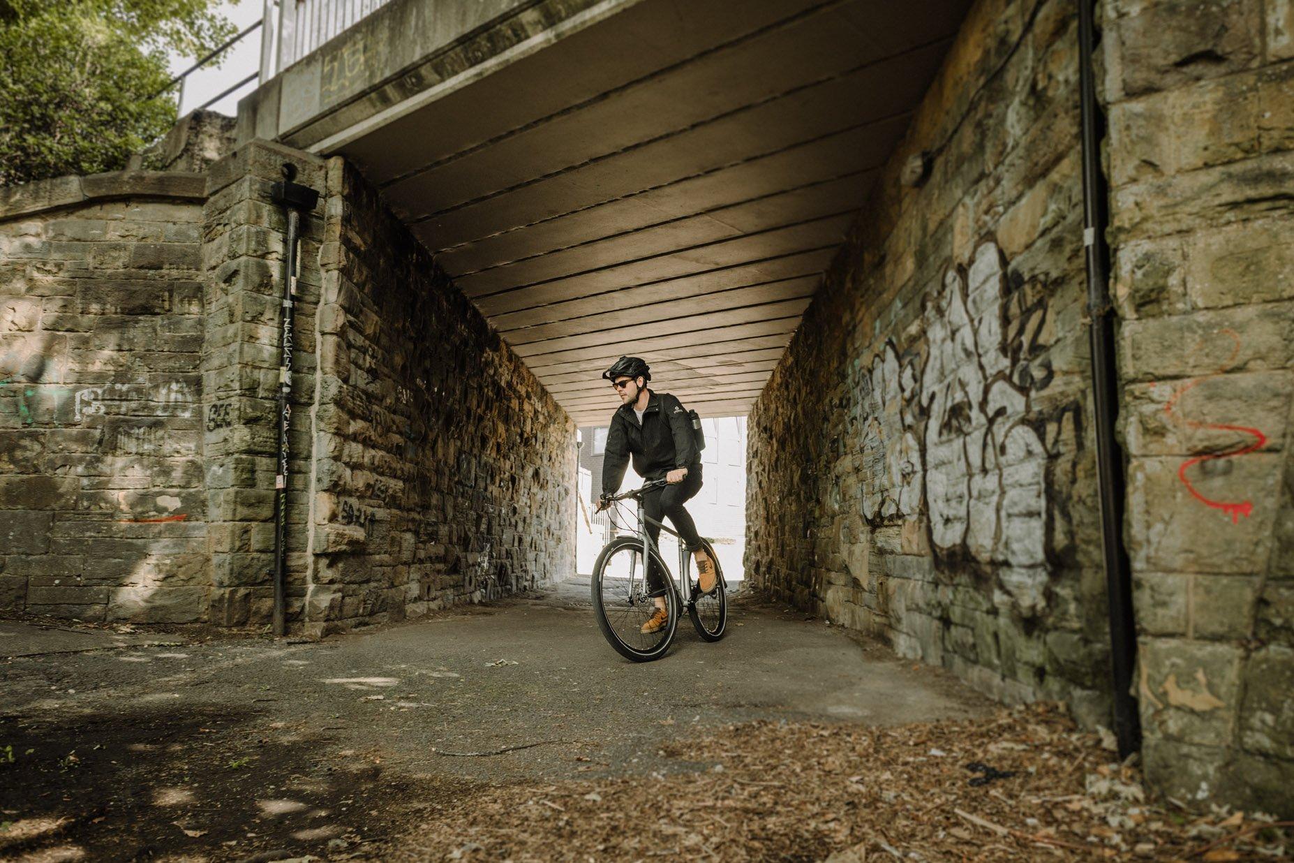 Commutor cyclist riding under bridge