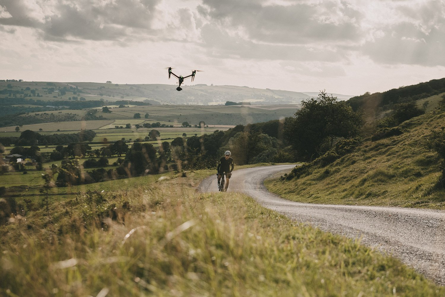 Cyclist riding up hill with drone following